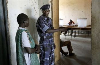 A south Sudanese woman is directed by a police officer to enter the polling room at a polling station in Lologo, Southern Sudan, Sunday April 11, 2010 (AP)