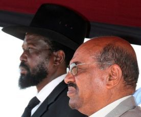 Sudanese President Omar al-Bashir (R) and southern leader Salva Kiir listen to the coutry's national anthem at Juba International airport on January 4, 2010 (Getty Images)