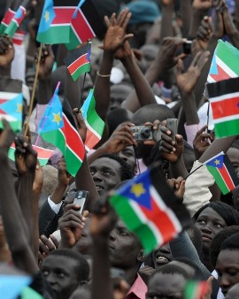 A large crowd of South Sudanese look up at a giant South Sudan flag being hoisted during a ceremony in the capital Juba on July 09, 2011 (Getty)