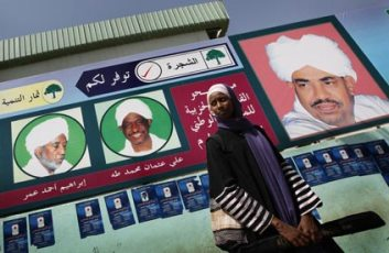 A Sudanese woman stands in front of an electoral poster for Sudan's ruling National Congress Party (The Guardian Website)