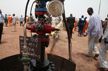 Oil mining employees walk near the first well to restart production in the Thar Jath field in Unity state on 6 April 2013 (HANNAH MCNEISH/AFP/Getty Images)