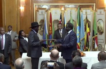 South Sudan's president Salva Kiir (L) and rebel leader Riek Machar (R) exchange the signed documents after reaching a peace agreement in the Ethiopian capital, Addis Ababa, on 9 May 2014 (AP)
