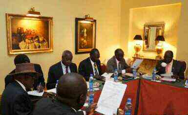 Negotiators at South Sudan peace talks in the Ethiopian capital, Addis Ababa, review a draft cessation of hostilities agreement on 13 January 2014 (Photo courtesy of Larco Lomayat)