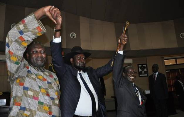 President Salva kiir(C) FVP; Riek Machar (L), and VP, Marilyn, raise their hands after swearing in ceremony of Machar on April 26, 2016. (Photo Lomayat Moses)